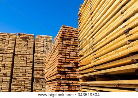 Many Piles Of Treated Pinewood Are Seen In The Yard Of A Construction Material Supplier. Thin Planks