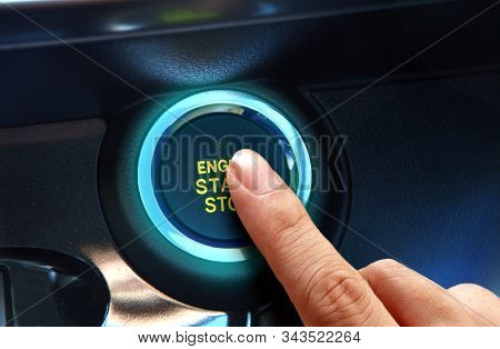 Finger Pressing The Start Or Stop Engine Button In Close Up.