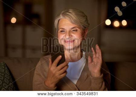 technology, old age and people concept - happy senior woman with smartphone having video call and waving hand at home in evening