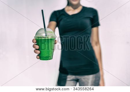 Green smoothie sports drink of vegetable detox cleanse juice in to go plastic cup woman giving takeout at caf?.