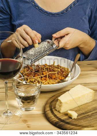 Photo Of A Woman Grating Parmesan Cheese Over A Bowl Of Traditional Spaghetti Bolognese With A Glass