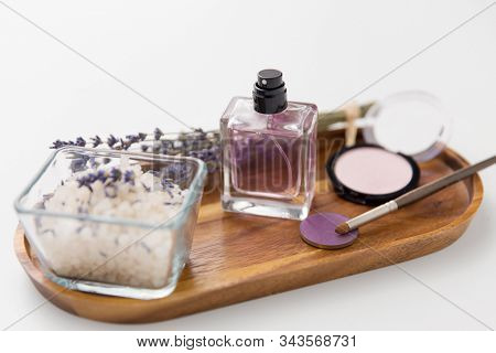beauty, make up and wellness concept - sea salt, perfume, lavender and mineral cosmetics on wooden tray