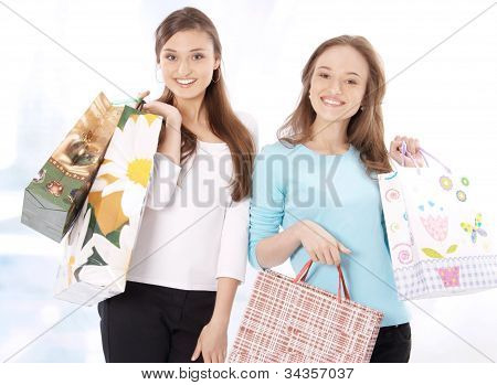 Portrait of stunning young women carrying shopping bags