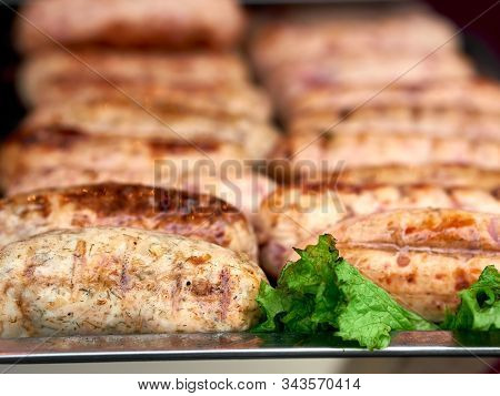 Rows Of Freshly Grilled Chicken Meat Sausages On Tray With Fresh Lettuce At Street Food Festival, Se