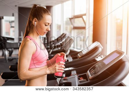 Slim Pretty Joyful Girl Jogging At The Treadmill And Holding A Shaker With Protein Cocktail In The G