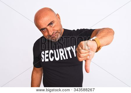 Middle age safeguard man wearing security uniform standing over isolated white background looking unhappy and angry showing rejection and negative with thumbs down gesture. Bad expression.