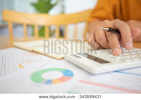 Close Shot Of Businesswoman Hands Holding A Pen Writing Something On The Paper On The Foregroundin