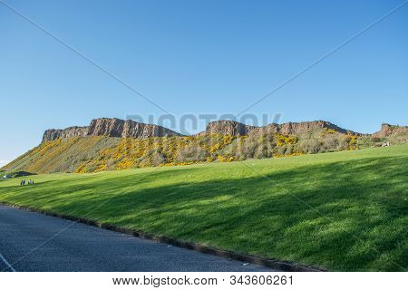 Edinburgh / Scotland / Uk - 04/20/2014: View Of Salisbury Crags On Holyrood Park With Green Spaces,