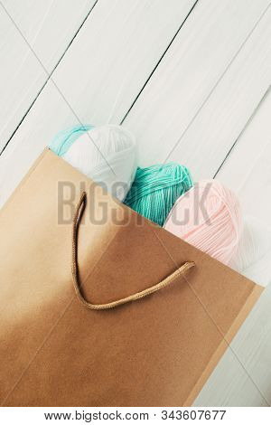 Scatter Oval Acrylic Colorful Wool Yarn Thread Skeins Lying With Kraft Paper Brown Package On White