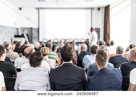 I Have A Question. Group Of Business People Sitting In Conference Hall. Businessman Raising His Arm.