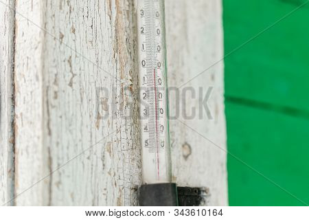 Old Outdoor Thermometer On A Wooden House With Zero Degrees, Closeup
