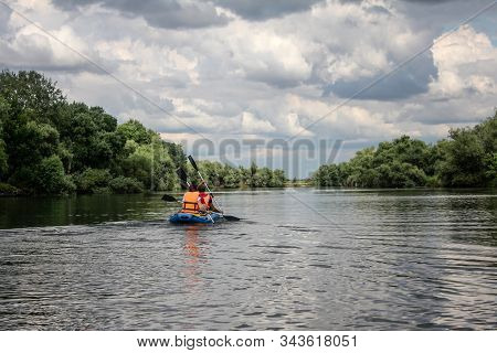 Family  Enjoy Water Rafting Activity At River. Rafting Family On Holidays. Group Of Adventurer Doing