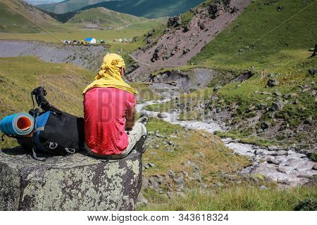 Man With A Backpack Is Sitting On A Halt In The Mountains.  Summer Ascent To The Elbrus