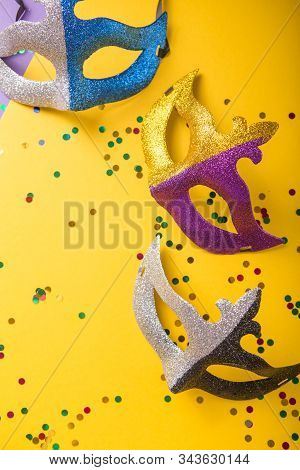 Mardi Gras Mask And Beads. A Festive, Colorful Group Of Mardi Gras Or Carnivale Mask On A Yellow Pur