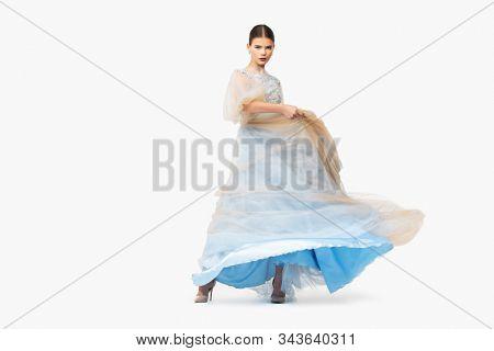 A full length portrait of a charming lady in a wedding dress posing in the studio. Wedding fashion, bride.
