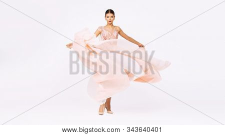 A full length portrait of a charming lady in a wedding dress posing in the studio. Wedding fashion, bride.