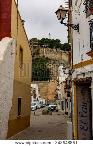 Denia, Alicante, Spain, November 21, 2018: Small Street In The Old Town Of Denia, With The Castle In