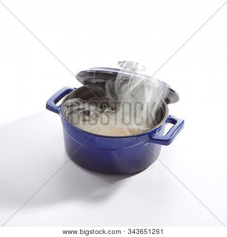 Homemade chicken soup with potatoes, carrots and onions in a blue pan isolated on white background side view. Traditional meat seasoned broth, sturdy clear bouillon in cook pot closeup
