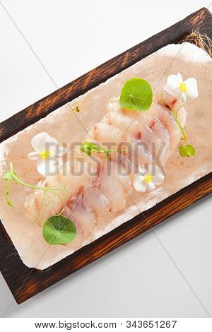 Sea perch ceviche or redfish cebiche on wood restaurant plate isolated. Raw rockfish fillet marinated in lime juice with spicy sauce, edible flowers and greens top view