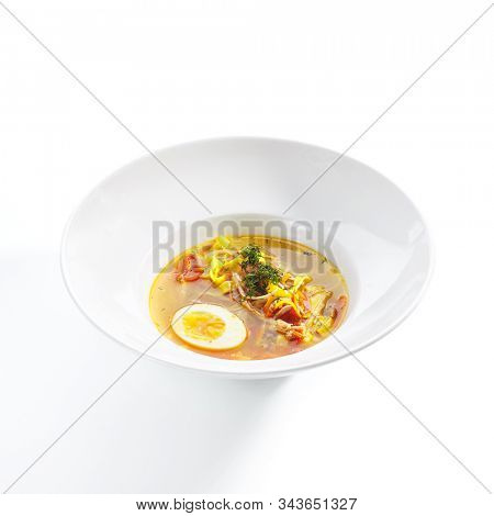 Chicken soup with tagliatelle pasta, eggs and fresh herbs isolated on white background side view. Delicious restaurant clear bouillon with poultry meat, vegetables and spices