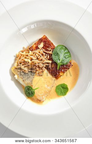 Baked halibut fillet with parsnip cream, fresh spinach and gourmet sauce on restaurant plate isolated. Grilled sea food, white fish, pollock or cod steak and deep fried onions topview