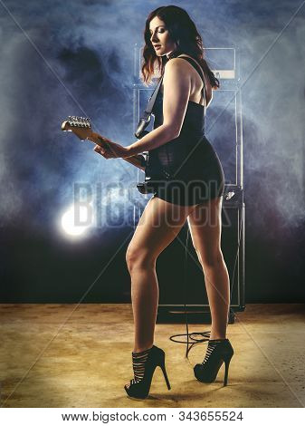 Young Beautiful Redhead Woman Wearing Short Dress And Playing An Electric Guitar In Front Of Large A