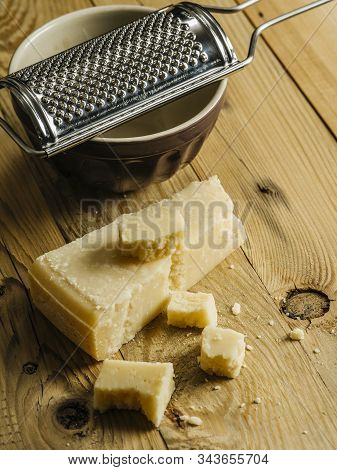 Block Of Parmesan Cheese On A Wooden Table With Grater In The Background.