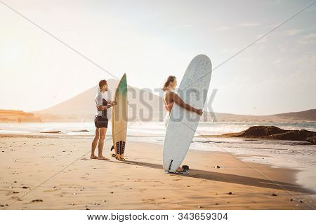 Surfers Couple Standing On The Beach With Surfboards Preparing To Surf On High Waves - Young People