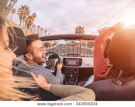 Happy friends having fun on convertible car during road trip - Group trendy young people enjoying vacation together in tropical city - Youth culture lifestyle and travel transportation concept
