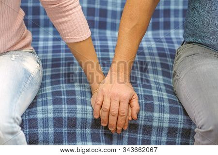 A Man Holds A Woman's Hand While