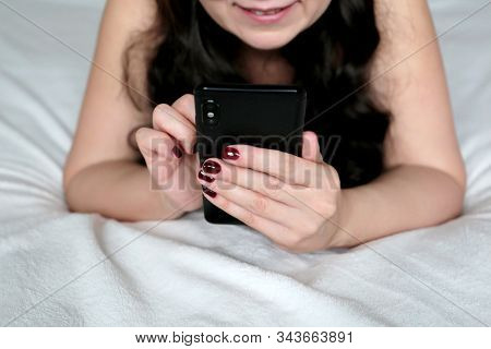 Smiling Woman With Long Curly Hair Lying On A Bed And Using Smartphone. Mobile Phone In Female Hands
