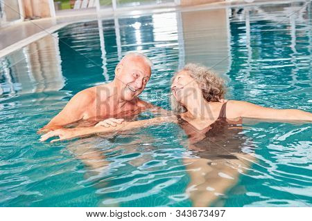 Happy senior couple has fun in swimming pool at the wellness hotel