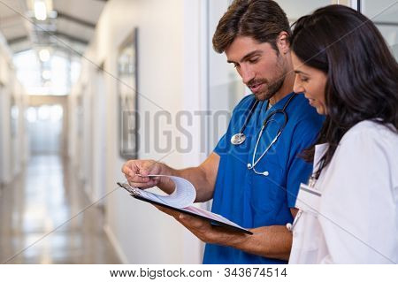 Team of doctors working together on patients file at hospital. Medical staff analyzing report and working at clinic. Woman doctor having discussion in a hospital hallway with nurse, copy space.