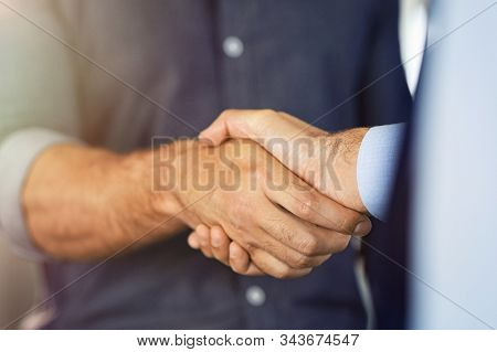 Close up of friendly handshake of business people. Business partners signing deal with handshake at office. Negotiation meeting for a successful merger, business agreeement.