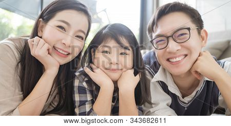 Portrait Of Happy Asian Family Spending Time Together In Living Room. Family And Home Concept