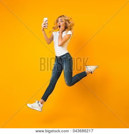 Overjoyed Girl Jumping And Looking At Phone, Shocked By News, Yellow Background, Crop