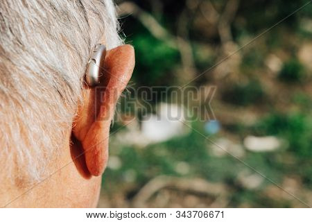 closeup of a caucasian senior man, seen from behind, wearing a hearing aid outdoors