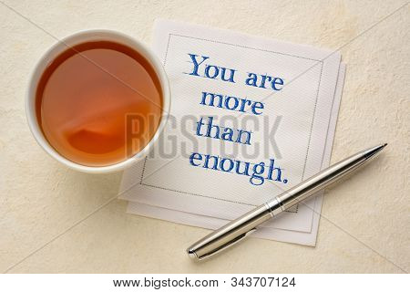 You are more than enough - inspirational handwriting on a napkin with a cup of tea, pep talk, self esteem and personal development concept