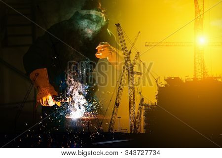 Double Exposure Of Craftsman Welder Is Welding Steel Frame On Construction Site Background, Welder M