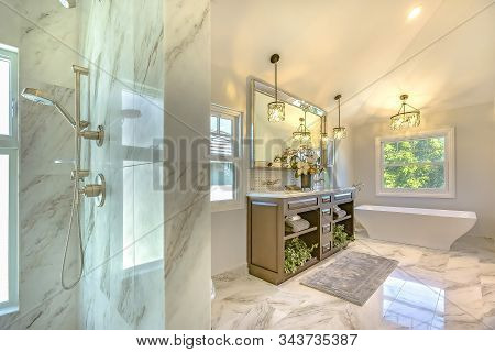 Luxury Bathroom With Marble Wall And Floor Decorated With Chandeliers And Plants