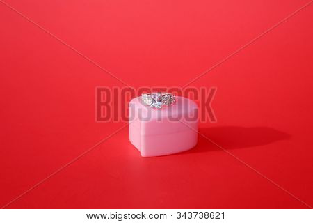 Engagement Ring. Wedding Ring. Platinum and Diamond Engagement or Wedding Ring in a Heart Shaped Ring Box. Isolated on Red. Room for text. clipping path. Wedding Rings are enjoyed world wide.