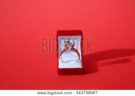 Man and Woman's Wedding Rings. Engagement Ring. Wedding Ring. Gold and Diamond Engagement or Wedding Ring on a Ring Box. Isolated on Red. Room for text. clipping path. Wedding Rings are enjoyed world