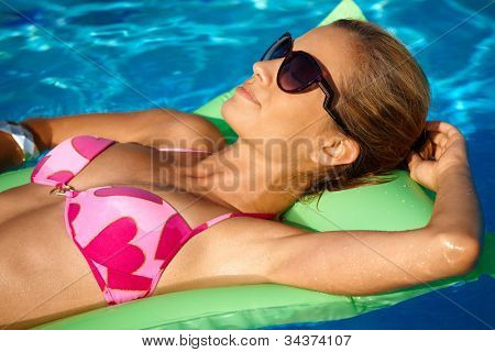 Young woman sunbathing in swimming pool at summertime, laying on airbed.