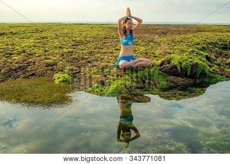 Young Woman, Meditating, Practicing Yoga And Pranayama At The Beach. Sunrise Yoga Practice. Hands Ra