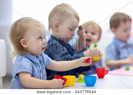 Kids Group Playing With Play Clay At Nursery Or Kindergarten Or Primary School