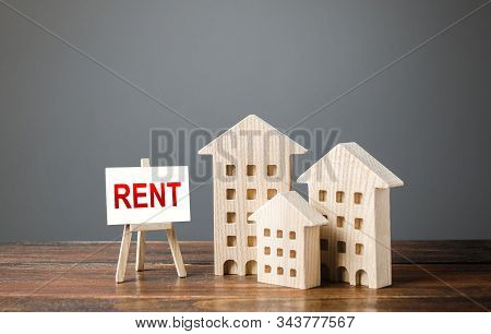 Three Figures Of Houses And An Easel With The Word Rent. Realtor Services, Search For Optimal Option