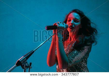 Caucasian Female Singer Portrait Isolated On Blue Studio Background In Neon Light. Beautiful Female