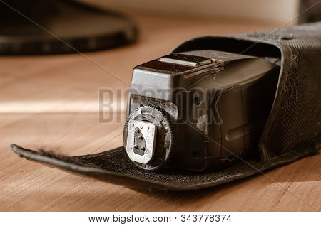 External Flash For The Camera In A Protective Case. Closeup Of A Black Used Flash For A Digital Came