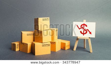 Pile Of Boxes And Easel With Dollar Red Arrow Down Graph Chart. Drop In Profits, Slowdown In Sales.