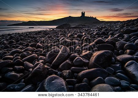 Dunstanburgh Castle In Northumberland England. The Castle, Now A Ruin, Occupies A Commanding Positio